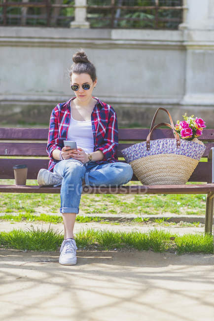 Front view of a young hipster woman sitting on a park bench relaxing in a sunny day while using a mobile phone — Stock Photo