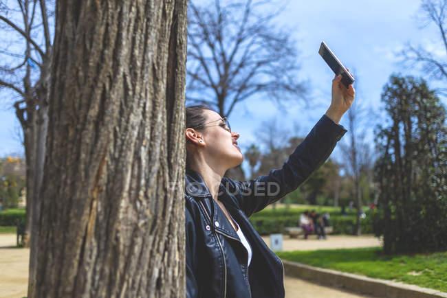 Seitenansicht einer Frau, die an einem sonnigen Tag im Park steht und sich an einen Baum lehnt, während sie ein Selfie mit ihrem Handy macht — Stockfoto