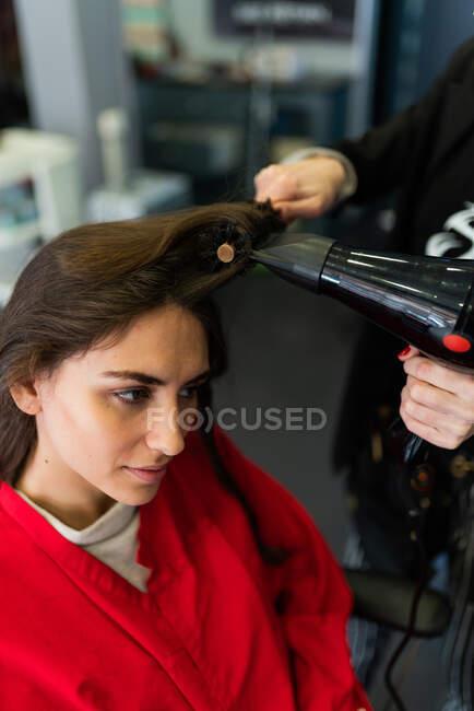 Crop stylist utilizzando asciugatrice e pettine e rendendo l'acconciatura alla donna attraente nel salone di parrucchiere — Foto stock