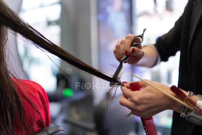 Mani di raccolto di stilista con forbici e pettine taglio capelli di donna nel salone di parrucchiere — Foto stock