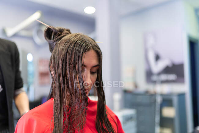 Aged stylist making hairdo to attractive young lady in hairdressing salon — Stock Photo