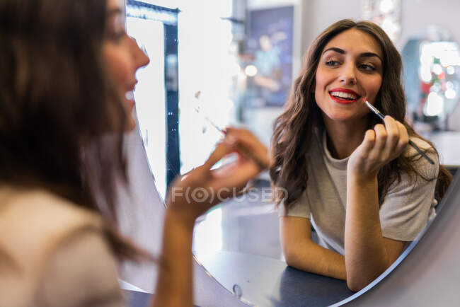 Reflection of young beautiful lady with hand near lips looking at mirror in hairdressing salon — Stock Photo