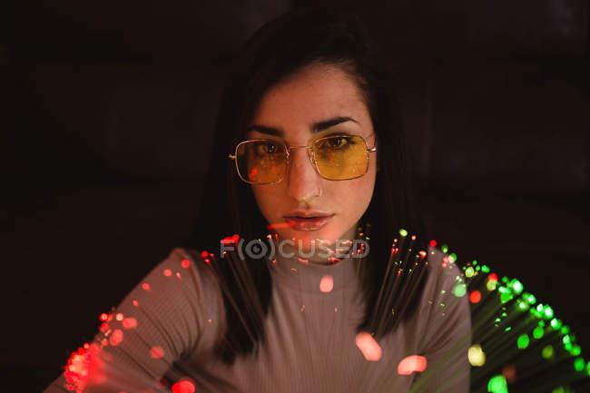 Mujer joven con luces de hadas en la oscuridad - foto de stock