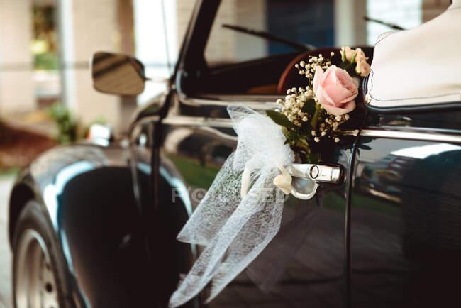 Hermosa rosa fresca colgando en el mango de cabriolet vintage en la calle - foto de stock