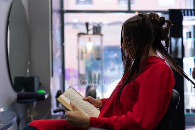 Вид сбоку привлекательной барышни, читающей громко и сидящей на стуле с красивой прической в парикмахерской — стоковое фото