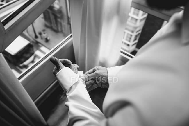 Чоловік застібає рукав сорочки. — стокове фото