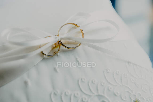 Von oben goldene Eheringe mit Schleife auf weißem Material — Stockfoto