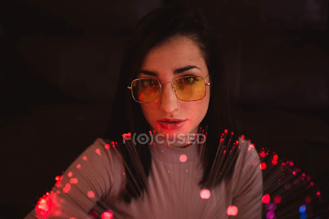 Young woman with fairy lights in darkness — Stock Photo