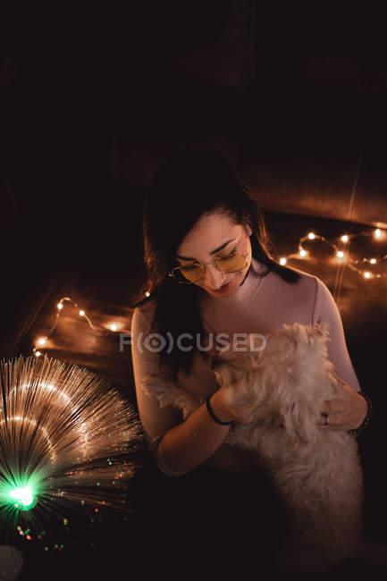Mujer joven con perro entre luces de hadas en la oscuridad - foto de stock