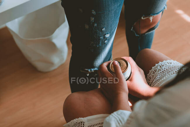 De cima senhora colheita em branco vestido segurando lata de bebida e sentado perto de mulher em jeans — Fotografia de Stock