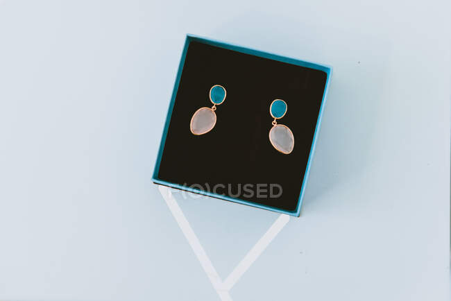 From above wonderful expensive earrings in blue box on grey background — Stock Photo
