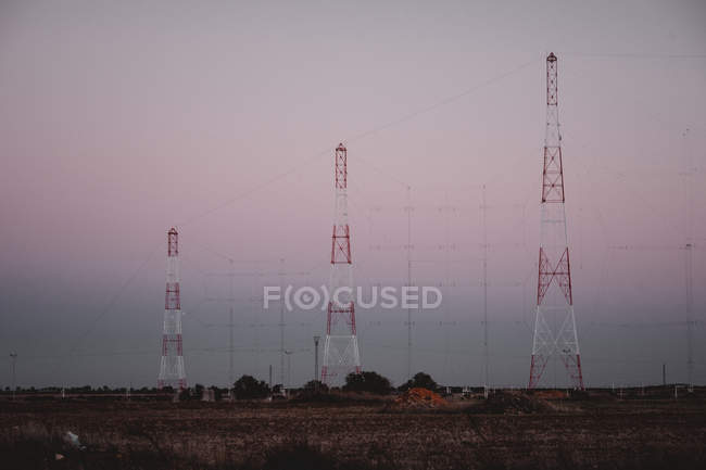 View to three red and white tall electric posts in field at sunset in Portugal — Stock Photo
