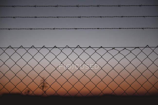 Vista através da cerca do elo da cadeia ao céu da noite — Fotografia de Stock
