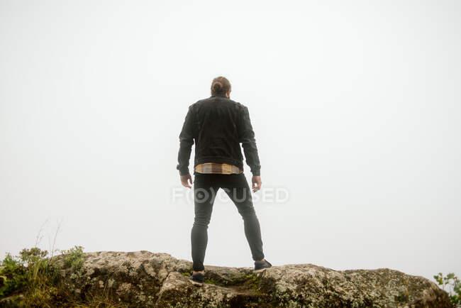 Hombre anónimo de pie en el acantilado cerca del camino rural - foto de stock