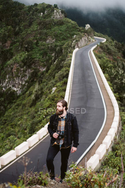 Bearded photographer looking away on mountain road — Stock Photo