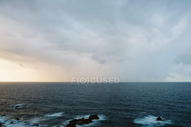 Vista mozzafiato del sole che sorge sul cielo nuvoloso sopra il maestoso mare increspato — Foto stock
