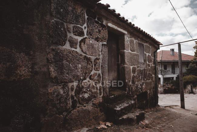 Vista al antiguo edificio de ladrillo y casa de pueblo en el campo - foto de stock