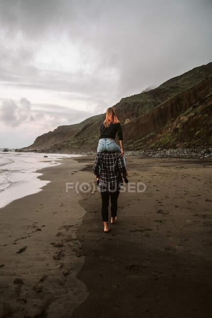 Vista trasera de tipo descalzo dando paseo a cuestas a la señora anónima mientras camina en la orilla del mar arenoso en el día nublado - foto de stock