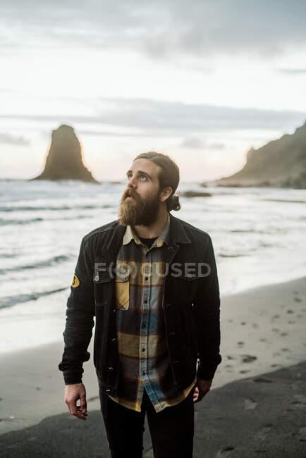 Стильный бородатый парень, выглядывающий на белый, стоящий на песчаном берегу у удивительного волнистого моря — стоковое фото