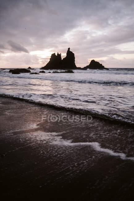 Самотня скеля в морі в похмурий день — стокове фото
