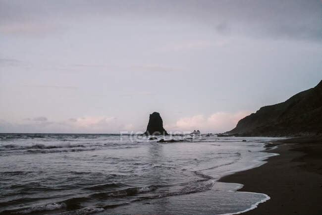 Lonely cliff in sea on cloudy day — Stock Photo