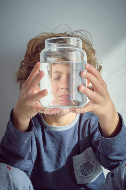 Cute little boy smiling and holding glass jar with clean water in front of face while standing against white wall — Stock Photo
