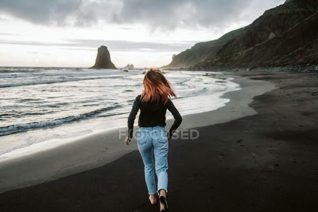 Vista posterior de la mujer descalza en traje casual corriendo sobre arena mojada cerca del mar tormentoso en el día nublado - foto de stock