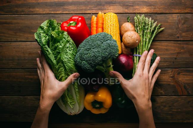 Mains humaines et légumes crus frais sur table en bois — Photo de stock