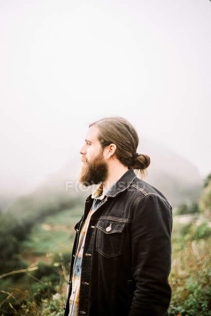 Vista lateral de cara barbudo bonito olhando para longe, enquanto em pé na natureza maravilhosa no dia nebuloso — Fotografia de Stock