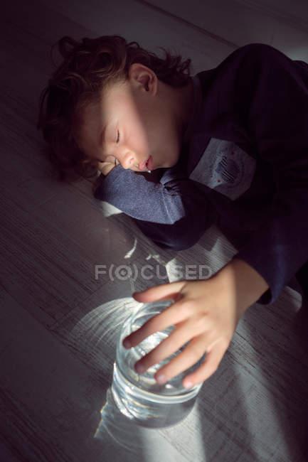 Chico encantador con vaso de agua limpia para dormir en el piso en casa - foto de stock