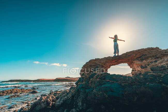 Нерозпізнавана жінка з витягнутими руками стоїть на грубій скелі біля величного моря проти яскравого блакитного неба в сонячний день. — стокове фото