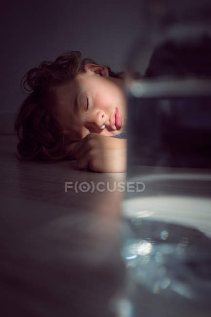 Cute little boy sleeping on floor near jar of water — Stock Photo
