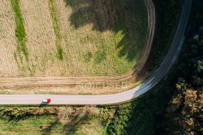 Беспилотный снимок современного микроавтобуса, едущего по асфальтовой дороге возле зеленого поля в солнечный день в сельской местности — стоковое фото