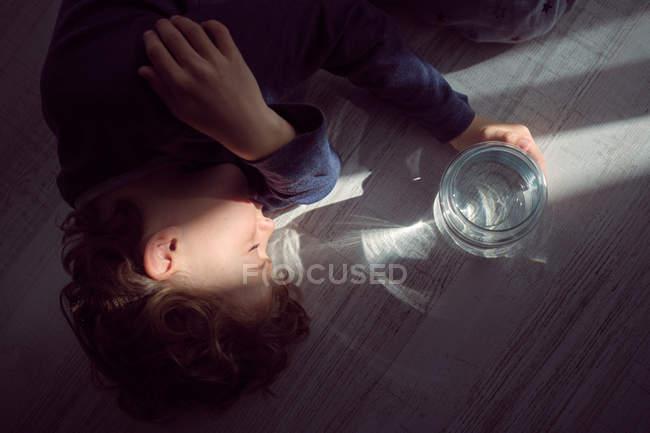 Lindo chico durmiendo en el suelo cerca del frasco de agua - foto de stock