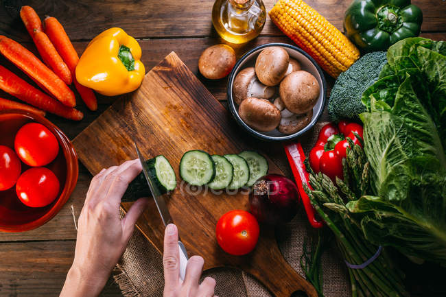 Human hands cutting fresh vegetables on wooden chopping board on kitchen table — Stock Photo