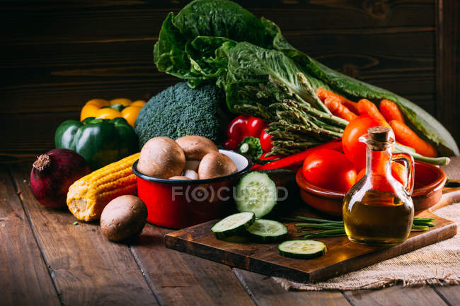 Assortment of fresh raw vegetables and utensils on wooden kitchen table — Stock Photo