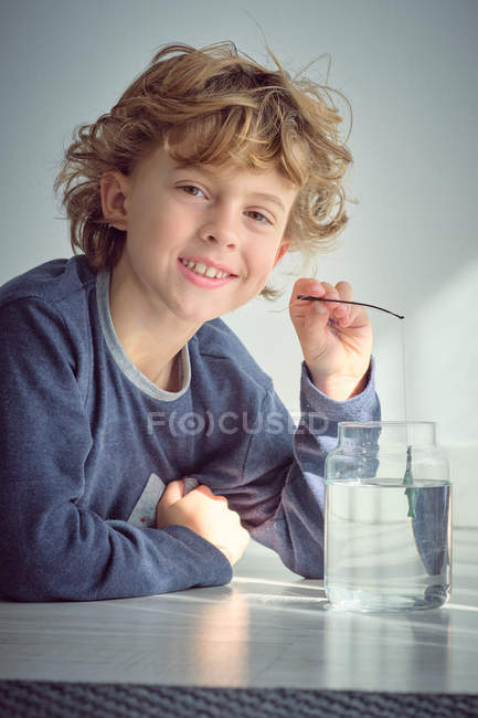 Portrait of smiling boy dipping small rod into vase with water — Stock Photo