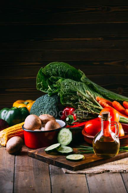 Surtido de verduras frescas crudas y utensilios en la mesa de cocina de madera - foto de stock