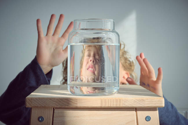 Cheerful boy gesturing behind vase of water on wooden stool — Stock Photo