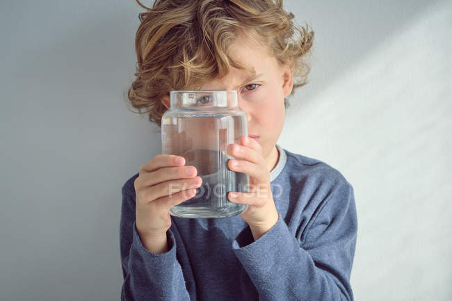 Boy holding vase of clear water in front of face — Stock Photo