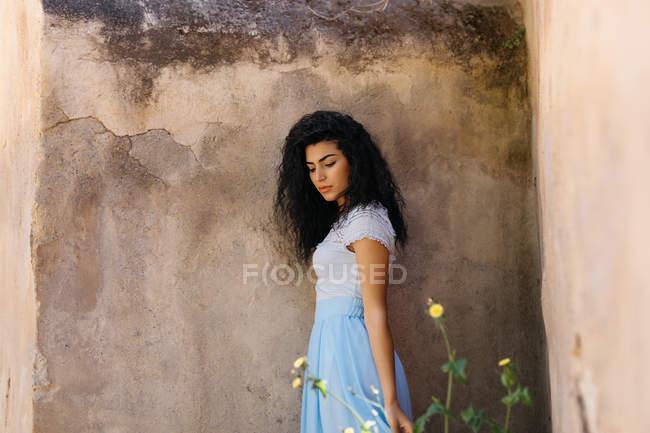 Beautiful woman near shabby wall — Stock Photo