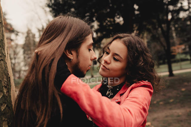 Long haired man hugging and kissing woman near tree — Stock Photo