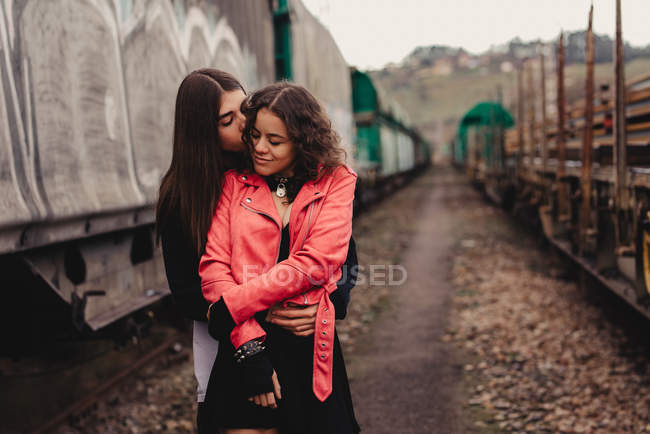 Long haired man hugging and kissing woman near train — Stock Photo