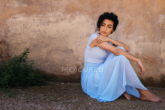 Красивая женщина рядом с потрепанной стеной — стоковое фото