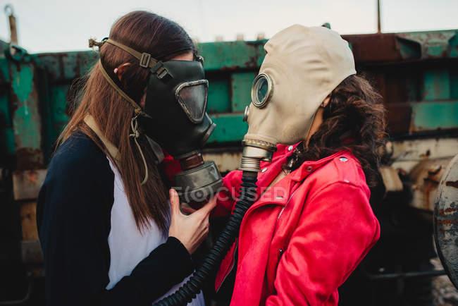 Vista lateral de jovens hipsters em moda desgaste e respiradores em pé perto de construção antiga — Fotografia de Stock