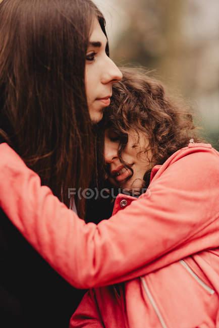 Hombre de pelo largo abrazando y besando a mujer cerca del árbol - foto de stock