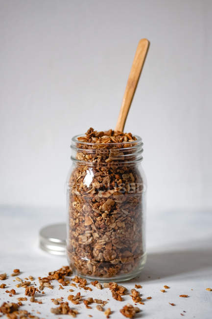 Jar of granola with wooden spoon on white background — Stock Photo