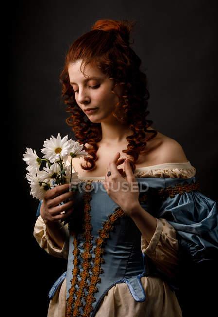 Бароко з заплющеними очима тримає купу квітів.. — стокове фото