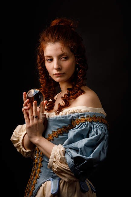 Baroque woman looking away while holding magical glass ball. — Stock Photo