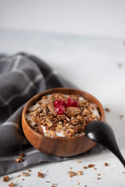 Yogurt with cereals and cranberries in wooden bowl on fabric — Stock Photo
